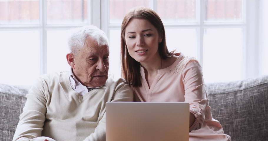Pretty young woman showing older mature father how to use computer at home. Smiling grownup daughter teaching explaining laptop applications to focused middle age senior dad, modern technology usage.