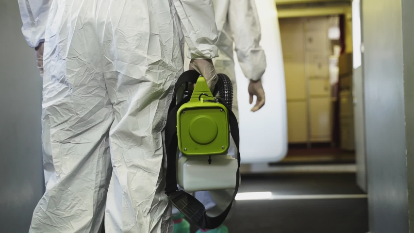 Cleaner officers hold cleaning device walking into airplane passenger cabin. An employee sprays disinfectant aboard a plane, during airline's sanitary prevention of the spread of Coronavirus pandemic. Royalty-Free Stock Footage #1053004445