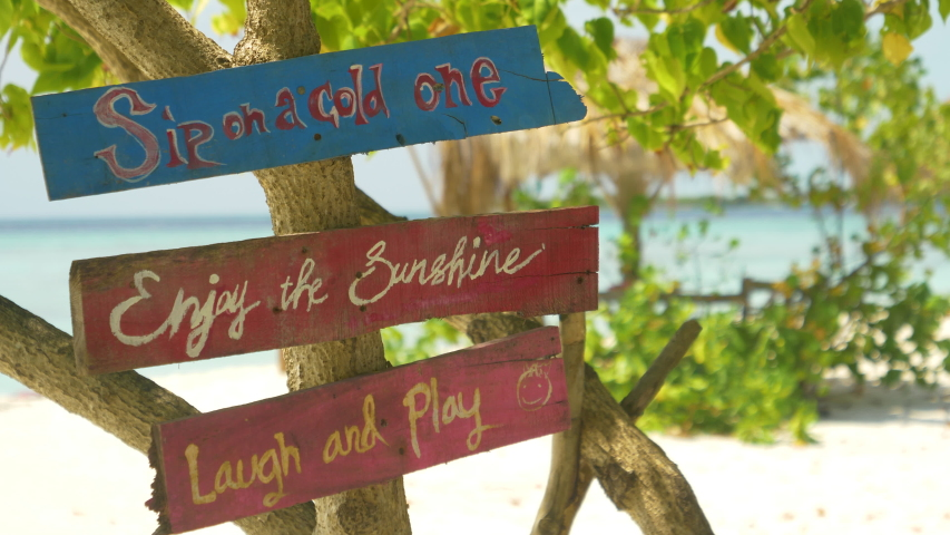 CLOSE UP, DOF: Vintage signs tell tourists to enjoy their day on the tropical beach. Colorful planks with positive sayings hang off a tree on a remote white sand beach in the picturesque Maldives. | Shutterstock HD Video #1053013025