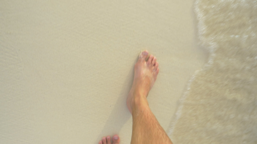 SLOW MOTION, POV: Looking down at your bare feet as you walk along the white sand beach washed by crystal clear ocean water. First person view of a man on vacation walking down a tropical sandy shore. | Shutterstock HD Video #1053013043