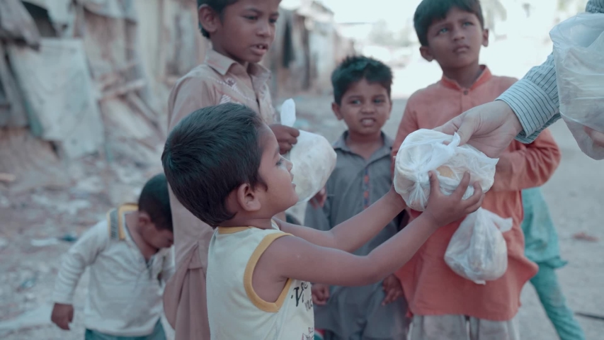 Poor hungry homeless children receive food from a kind person during the lockdown because of the coronavirus pandemic in Karachi, Pakistan. 22nd April 2020.