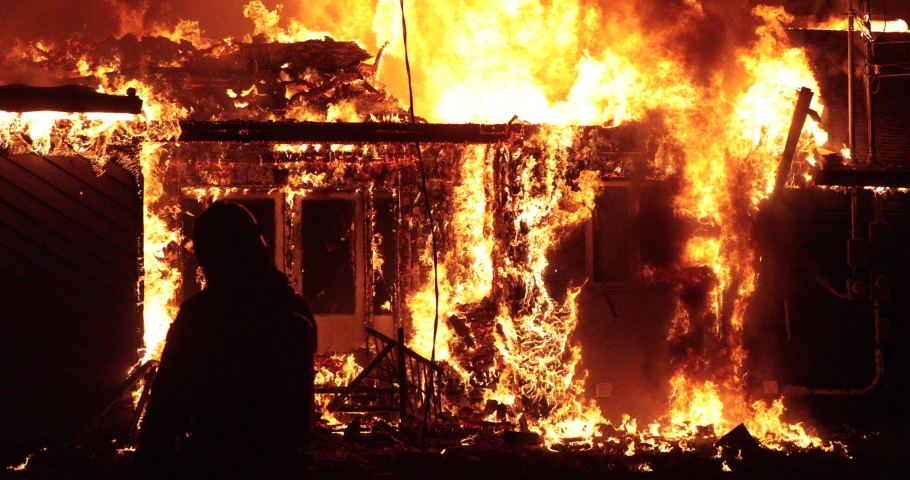 Quebec, Canada - May 2020 - Fully engulfed house fire. Firefighter in shadow in front of fire