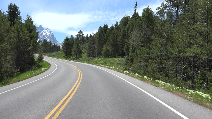 GRAND TETON, WYOMING - JUN 2015: Driving POV beautiful Grand Teton Mountain range forest 4K. Drive vacation travel point of view from vehicle. Destination for mountaineering, hiking, fishing. | Shutterstock HD Video #10530146