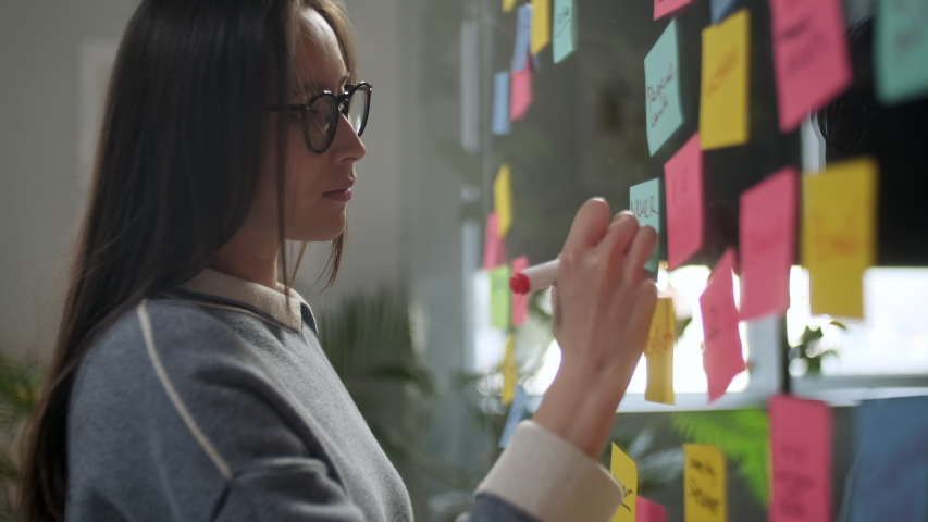 Asian Business Woman Write Tasks Creative Ideas On Sticky Notes On Glass Board, Female Corporate Leader Planning Project On Post It Sticky Notes Organize Work On Stickers | Shutterstock HD Video #1053015059