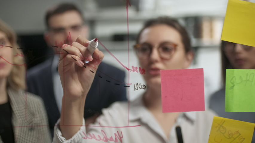 Young Business Team Brainstorming. Business Woman Draws a Graph On Glass Wall With Stickers. Colleagues Approve. Business Success Concept Royalty-Free Stock Footage #1053015074