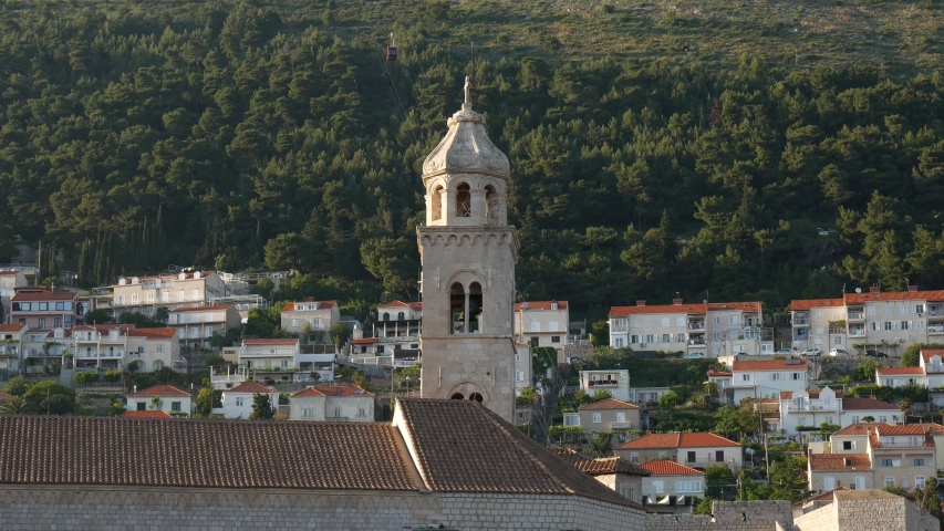 The bell tower of the Dominican monastery on the background of modern Dubrovnik, Croatia.
