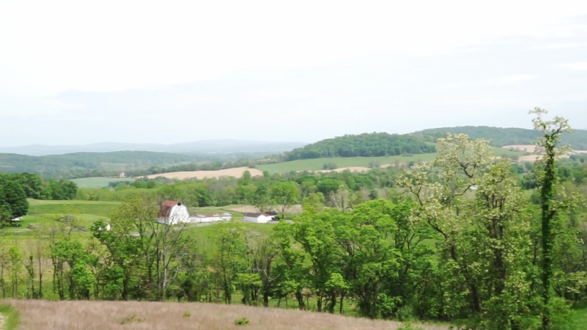 Farmhouse background viewed from hilltop above. Gentle breeze serenely moves the long grass and leaves of the foreground field. Video shot in Sky Meadows State Park in Paris, Virginia.   | Shutterstock HD Video #1053019913