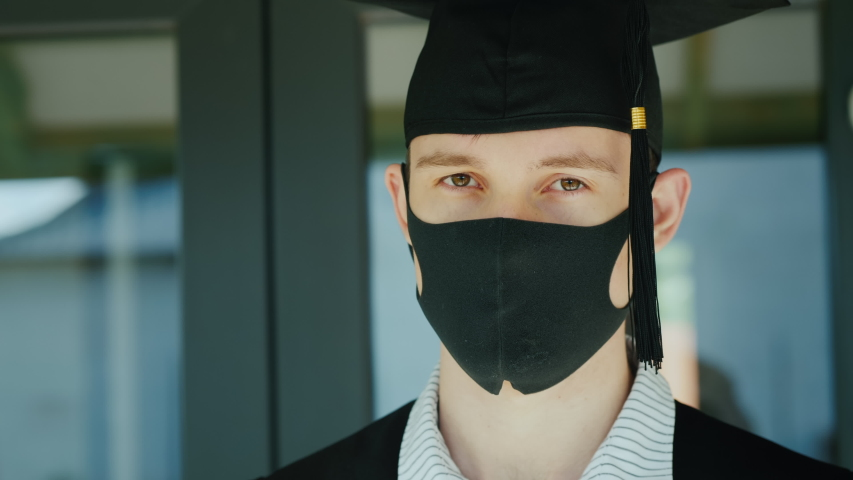 Graduate in a protective mask and cap, graduating from college under quarantine Royalty-Free Stock Footage #1053024923