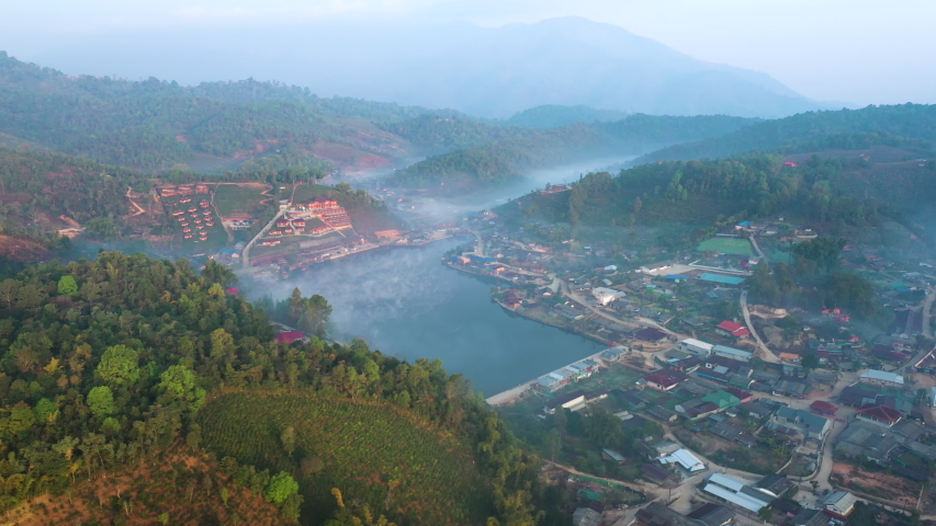 Aerial drone sky view flying in misty morning at Ban Rak Thai, a Chinese settlement in Mae Hong Son province, Northern Thailand. | Shutterstock HD Video #1053026444