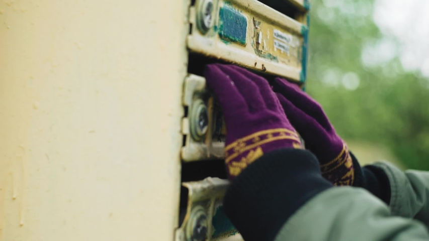 A man tries to look into a closed mailbox. Close - up of hands. Investigation   Shutterstock HD Video #1053028556