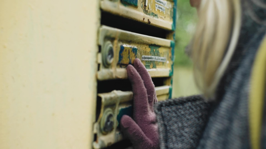 A girl inspects an old mailbox on the street. Side view. Close up   Shutterstock HD Video #1053028559