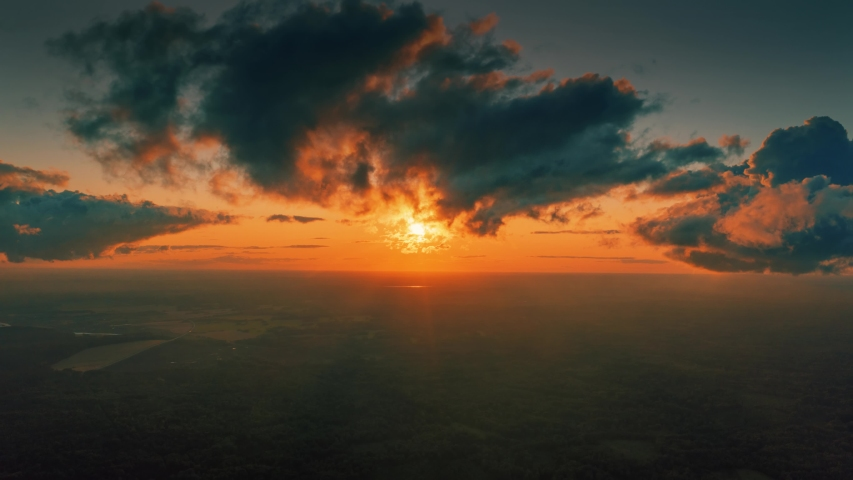 Aerial view of epic dark clouds flying into camera, revealing scenic sunset sun setting into horizon. Timelapse, 4K UHD.  | Shutterstock HD Video #1053040007