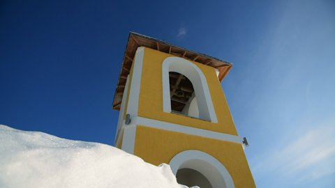 man in fluttering fur coat or mantle, black boots, hat and with beard jums to the snow from the yellow church bell tower with blue sky at the background. 4k. sunny winter day at Carpathian mountains