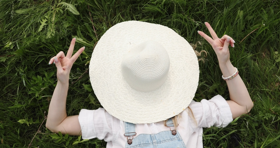 Woman with curly hair lies on the green grass and covers her face with a hat