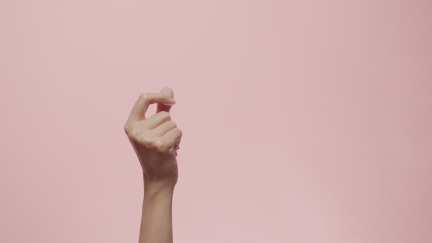 Close up of Woman's hand snapping her finger doing the hand gesture isolated on a pink studio background with copy space for place a text, message for advertisement, and promote your brand and product Royalty-Free Stock Footage #1053044465
