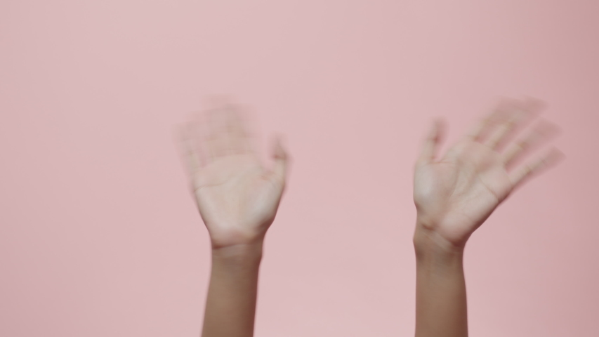 Close up of Woman's hands waving saying greeting, goodbye making hand gestures isolated on a pink studio background with copy space for place a text, message for advertisement, and promotional