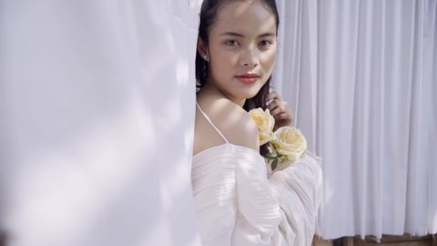 Beautiful Asian woman stands in front of drying white sheets with white roses in her hands. She enjoys wearing a fine white dress.
