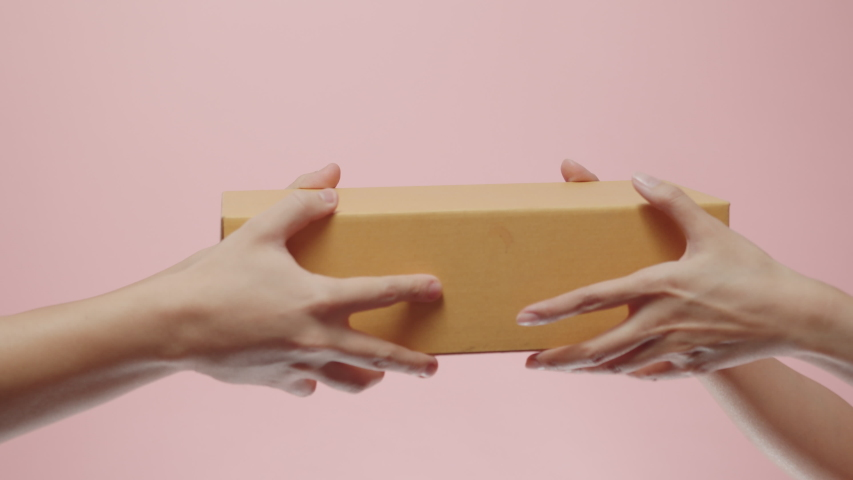 Close up of Woman's Hand Receive a parcel cardboard box from a delivery man who gives her Postal Package Box isolated on a pink studio background. Shipping and Delivery Concept.