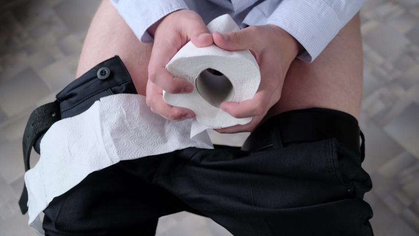 Discomfort, pain during bowel movements in a man in the toilet, close-up. Concept: hemorrhoids, colon tumor, irritable bowel syndrome, diarrhea, poisoning