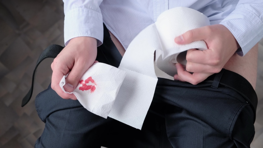 A man with hemorrhoids squeezes toilet paper with blood. Concept: hemorrhoids, colon tumor, irritable bowel syndrome, diarrhea, poisoning
