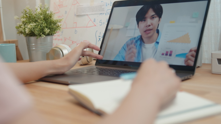 Businesswoman using laptop making video call conference with colleagues and talking, discussing business project online while she taking note on paper, write a report working from home and Remote work Royalty-Free Stock Footage #1053057650