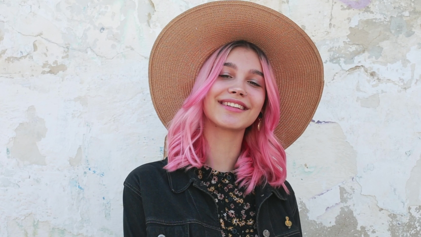 Beautiful positive young woman with a smile with a hat in a black denim jacket near a white wall on the street. Cheerful young teenager girl with pink hair outdoors. Happy emotion