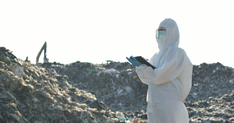 Asian female scientists or biologists in protective suits is standing in landfill and write examines research data on paper in slow motion. Global warming, Ecology, Enviroment pollution concept.  | Shutterstock HD Video #1053073898