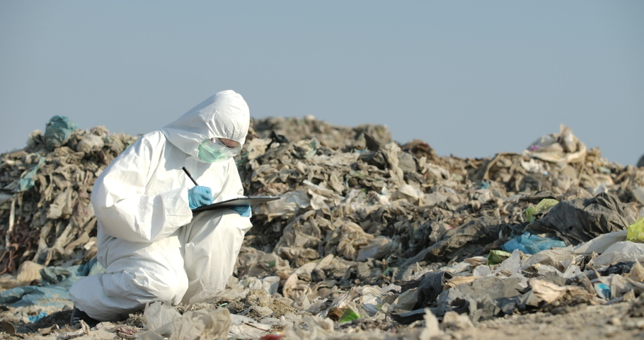 Asian female scientists or biologists in protective suits is standing in landfill and write examines research data on paper in slow motion. Global warming, Ecology, Enviroment pollution concept.  | Shutterstock HD Video #1053073904