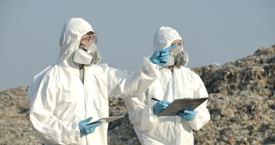Two asian male and female scientists or biologists in protective suits is standing in landfill and write examines research data on paper in slow motion. Global warming, Ecology, Enviroment pollution. | Shutterstock HD Video #1053073913