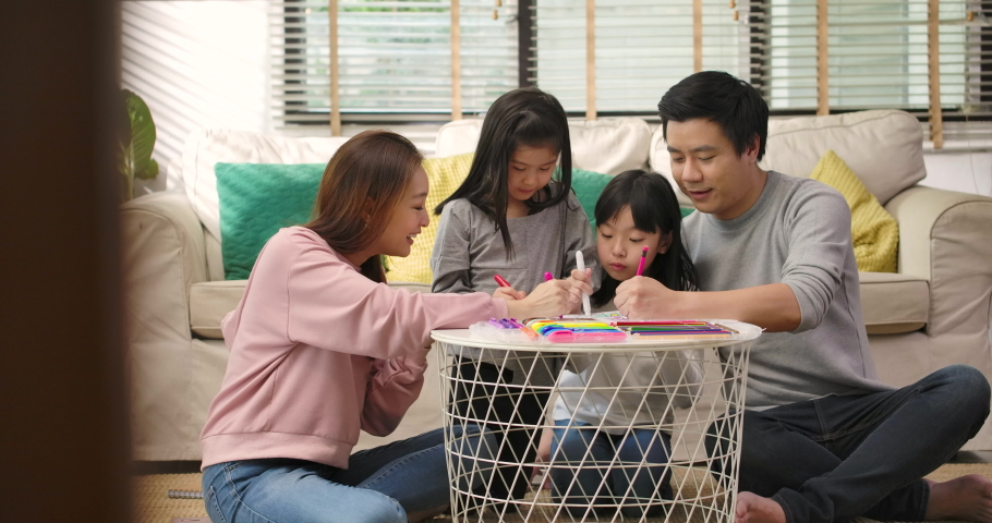 Happy young asian family parents and cute little children drawing coloring picture with pencils helping cute child daughter enjoying talk play at home, mom dad and kid girl having fun in living room.