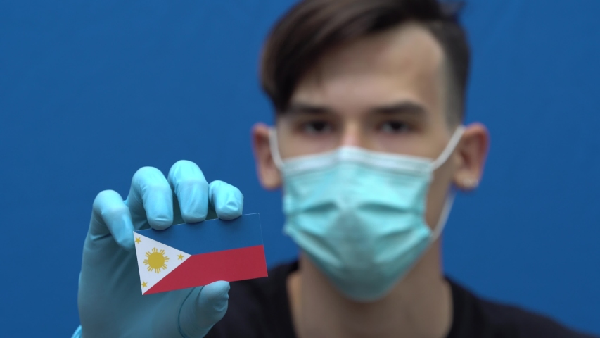 COVID-19 pandemic in Philippines. A young, attractive asian man, Filipino, in protective medical mask and gloves holding the flag of Philippines. Coronavirus pandemic in Asia | Shutterstock HD Video #1053075521