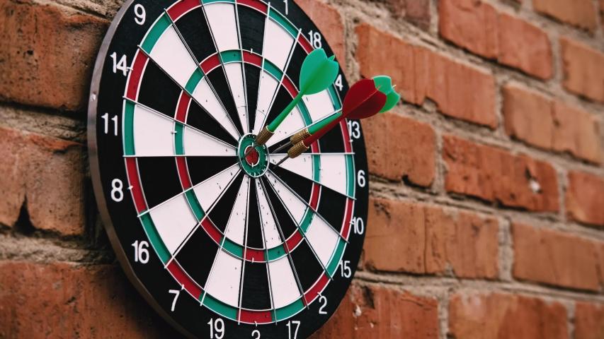 Three darts hit the target of a dart board. Bad shots on target of a dart board. | Shutterstock HD Video #1053080030
