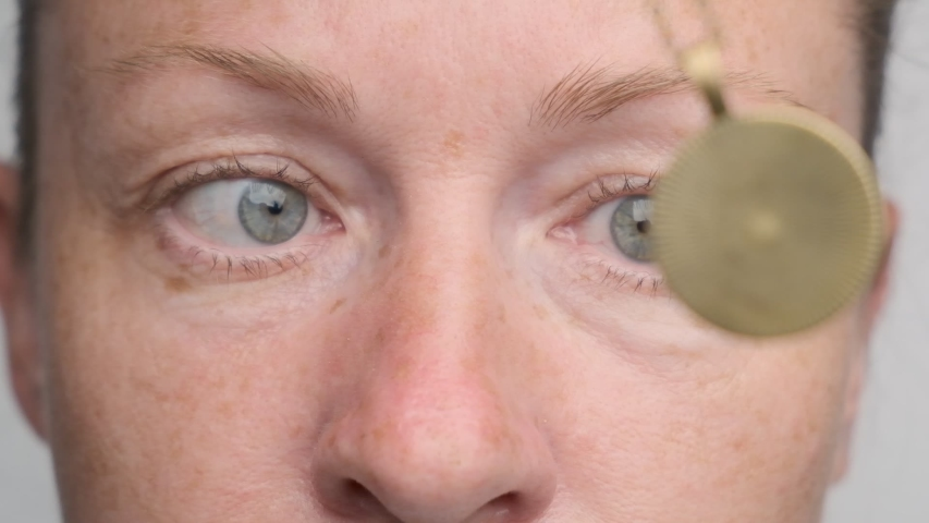 Man falls asleep in hypnosis session. woman's eyes follow swing of hypnotic pendulum and close.