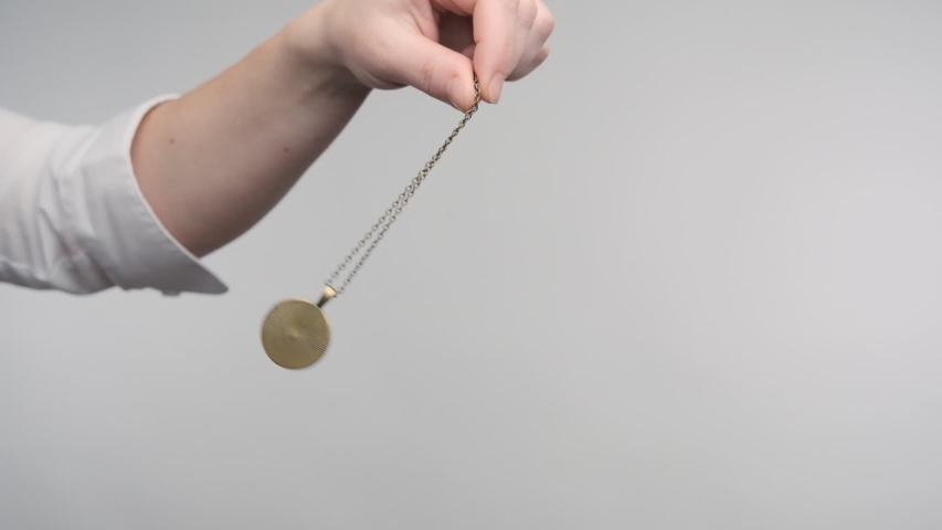 Hypnosis session pendant on chain sways in female hand of hypnotist.   Shutterstock HD Video #1053080102