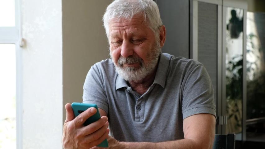 Happy senior elderly man holding smart phone watching mobile video calling online looking at screen