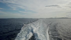 View from deck of boat ferry traveling from Coron to El Nido overlooking powerful water jetstream by boat engine with green mountain islands and deep blue ocean water. 30fps realtime UHD video H.264