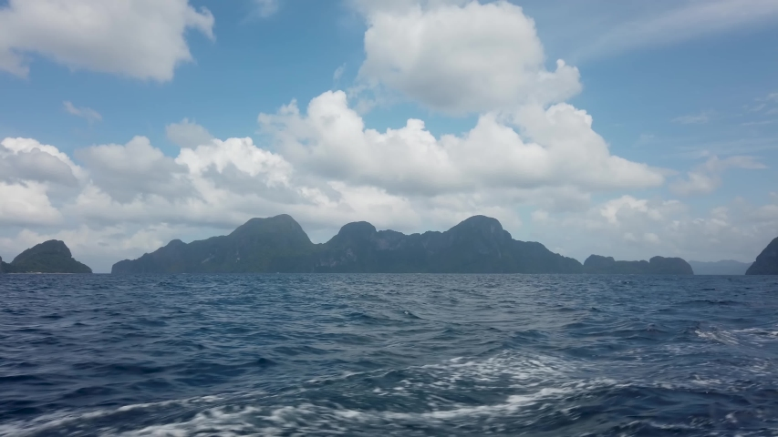 View from deck of boat ferry traveling from Coron to El Nido overlooking green mountain islands and deep blue ocean water waves from boat. 30fps realtime UHD video H.264