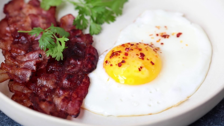 Keto breakfast - fried egg, avocado and fried bacon in white plate. Keto diet concept. Royalty-Free Stock Footage #1053088400