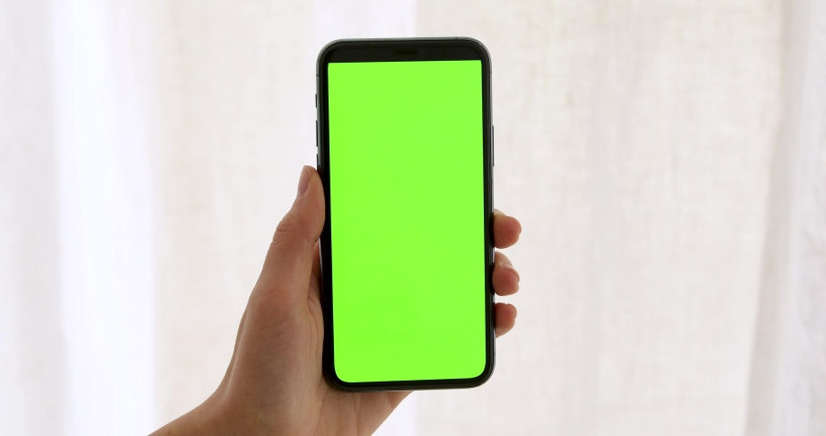 Close-up of a woman's hand holding green mock-up screen smartphone. Modern mobile phone. In the background cozy white curtain | Shutterstock HD Video #1053090221