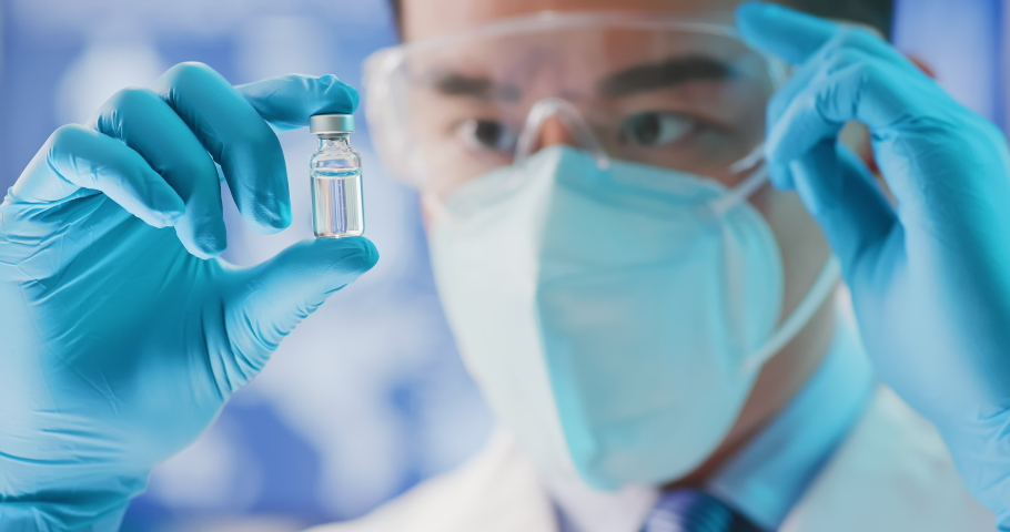Close up of scientist microbiologist or medical worker look to newest vaccine in the laboratory | Shutterstock HD Video #1053092159