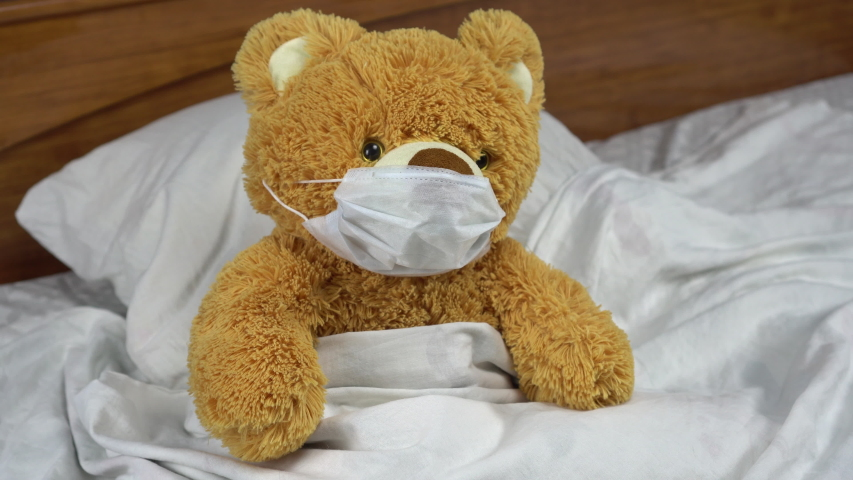A teddy bear measures the temperature with a mercury thermometer. The doctor puts a thermometer to the bear. The bear lies in bed with a medical mask.