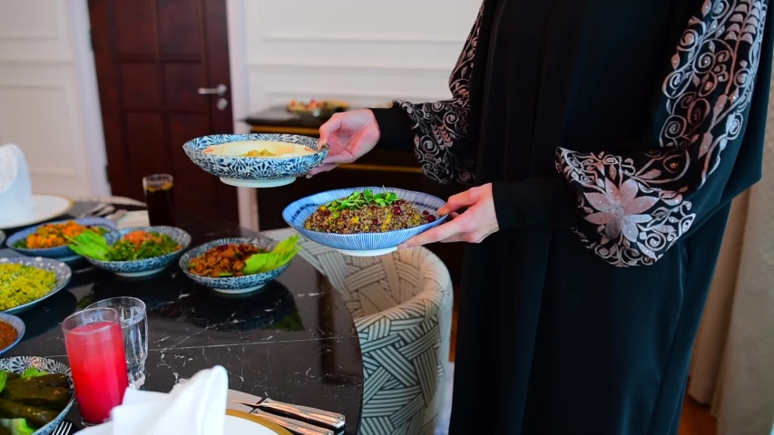 The Islamic holiday of Eid ul-Fitr marks the end of the Islamic fasting of the month of Ramadan.Traditional Eastern food and meal are on the table. Woman puts a plate of food on the table