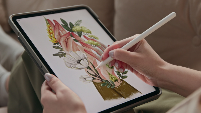 Art of young woman drawing ecological image of flowers in hands at display of digital notepad. Artist sketching colour painting by stylus at tablet computer closeup. Girl in comfort of home interior Royalty-Free Stock Footage #1053097700