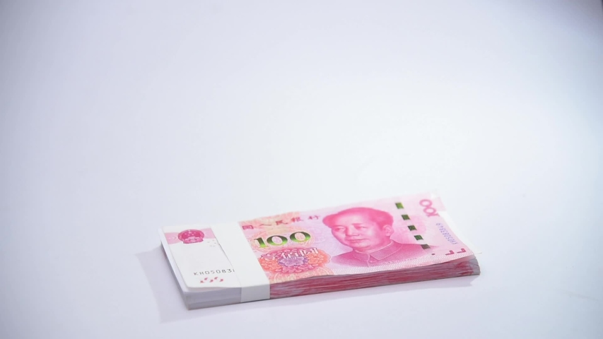 Chinese currency banknote packs drop on white counter table | Shutterstock HD Video #1053097979