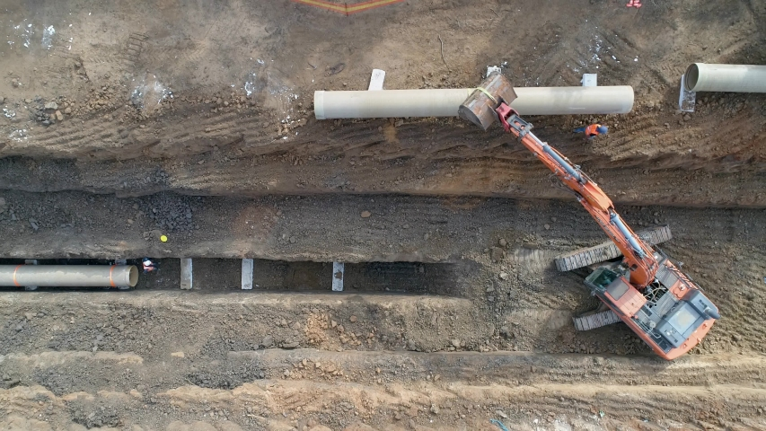 Concrete pipe tube installation. Aerial above men at work outside with heavy machinery to connect and install water or sewerage pipeline in a digging soil land