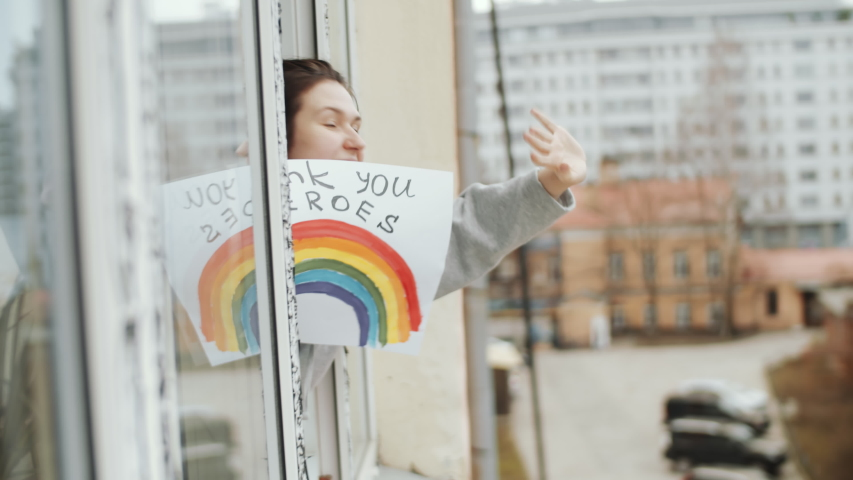 Young cheerful woman holding poster with inscription «NHS thank you heroes», looking out of the window, smiling and waving while expressing respect to healthcare workers during covid-19 pandemic
