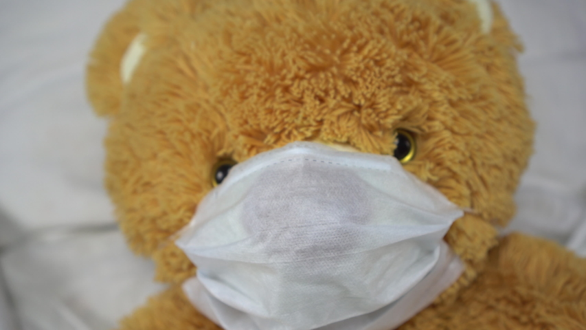 A teddy bear lies in bed in a medical mask. The bear got sick.