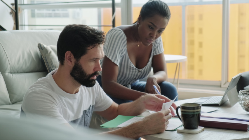 Multiethnic couple filing tax return, preparing home budget. African American woman and Caucasian man checking utility bill and banking account. Married people preparing taxes and form | Shutterstock HD Video #1053104507