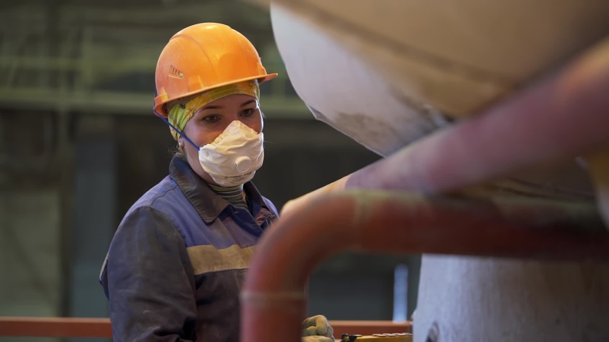 Portrait of a women worker at the factory. Stock footage. Female wearing protective face mask and an orange helmet while standing and controlling working process near machine at the industrial plant.
