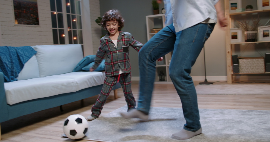 Young asian father and his son with curly hair playing football. Funny man dribbling the ball, enjoying his time together with kid - happy family, recreational pursuit concept 4k footage